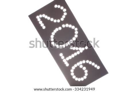 Light passes through the holes laid out in the form of number 2016. The sign on a light background. Blured.
