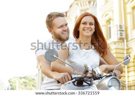 Light photo of a happy young couple sitting on a silver retro scooter. Red-haired girl holding a handlebar and her bearded boyfriend sitting behind her - stock photo