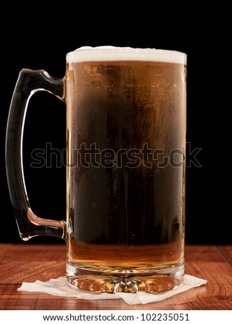 light pilsner served in a frosted mug isolated on a black background - stock photo
