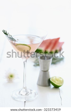 Light pink cocktail mocktail in a martini glass decorated with a slice of lime and garnish with a slice of watermelon and flowers in the background - stock photo