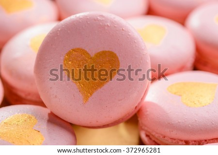 Light pink macaroon decorated with a heart of gold close-up. A gift on Valentine's Day. - stock photo