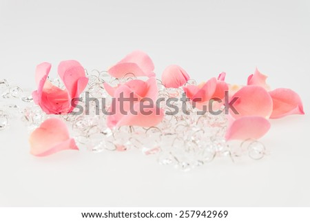Light pink rose petal with crystal on white background - stock photo