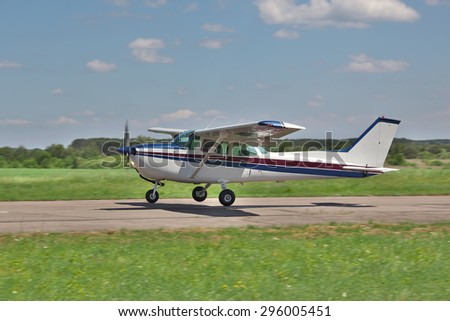 Light plane landing or taking off on the runway on the airfield - stock photo