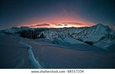 Light pollution glows with a certain beauty against the starry night sky.  This image was taken after a snowshoe trek above Loveland Pass, west of Denver, Colorado. - stock photo