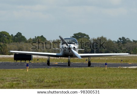 Light private airplane on the ground front view - stock photo