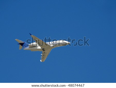Light private jet airplane against blue sky - stock photo