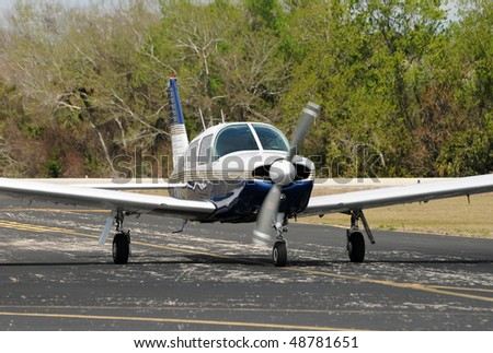 Light private propeller airplane taxiing on the ground - stock photo