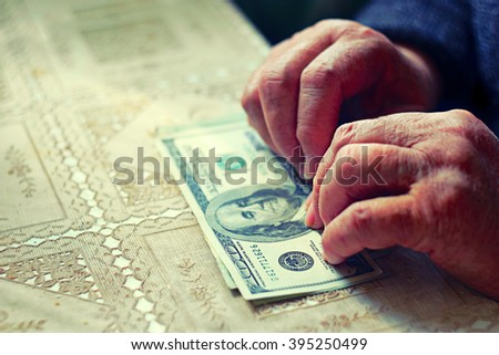 Light purse. Senior woman with hundred dollar bill, selective focus, toned image. Very shallow DOF. Colorized shot. - stock photo