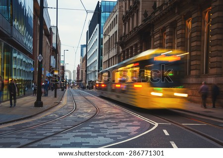 Light rail Metrolink tram in the city center of Manchester, UK in the evening. The system has 77 stops along 78.1 km and runs through seven of the ten boroughs - stock photo