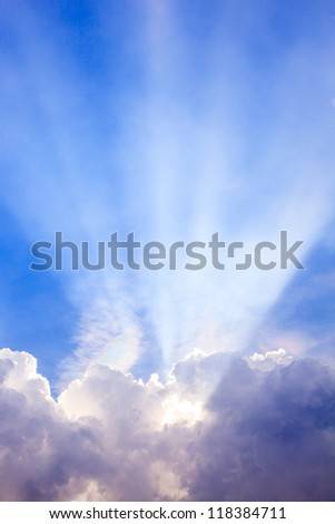 Light ray from sun behind cloud in the blue sky - stock photo