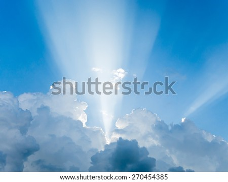 Light rays shine through clouds