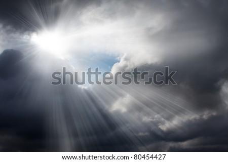Light rays shine through the dark clouds - stock photo