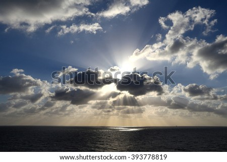 Light rays shine through the group of clouds - stock photo