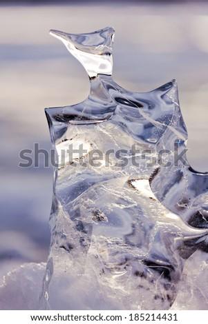 Light reflections in clear ice sculpture shaped by nature through repeated thaw and frost cycles - stock photo