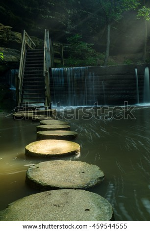 Light shining on the stepping stones in Matthiessen State Park on a Summer's morning.  Illinois, U.S.A.. - stock photo