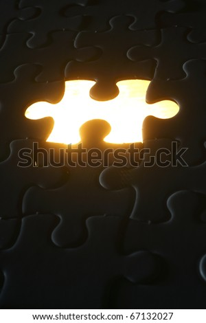 Light shining out of a missing puzzle piece. - stock photo