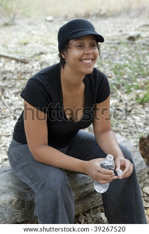 light skinned african-american woman taking a playful rest with a bottle of water - stock photo