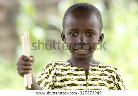 Light Smile on African Black Boy. Little African boy smiling whilst holding up a bunch of pencils for an educational symbol for Africa. Beautiful education background with copy space. - stock photo