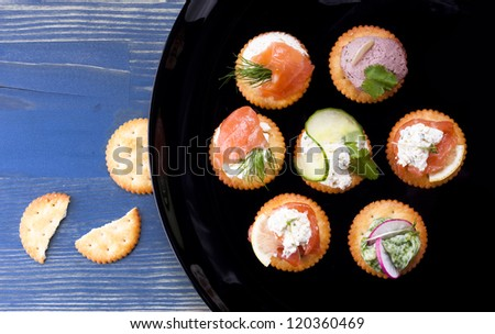 Light snack from various ingredients with soft cheese and herbs on crackers. - stock photo