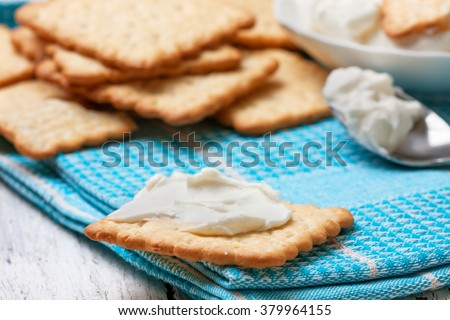 light snack of crackers and cream cheese on blue napkin  - stock photo