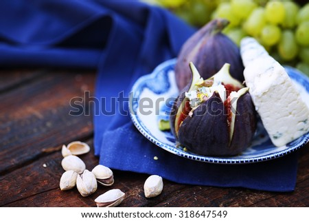 Light snacks of cheese, figs, grapes, pistachio - stock photo