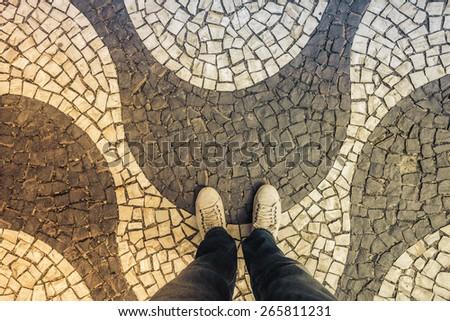 Light Sneakers shoes walking on Copacabana mosaic sidewalk top view, Rio de Janeiro - stock photo