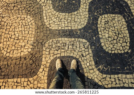 Light Sneakers shoes walking on Ipanema Beach mosaic sidewalk top view, Rio de Janeiro - stock photo