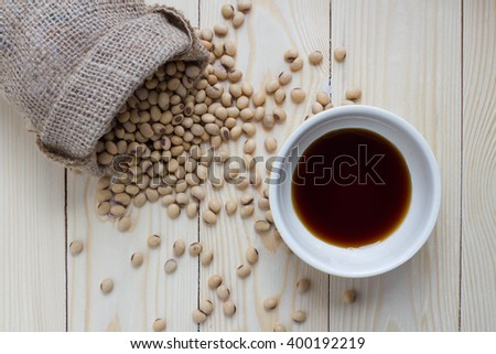 Light Soya sauce in bowl and soybeans on wooden background - stock photo