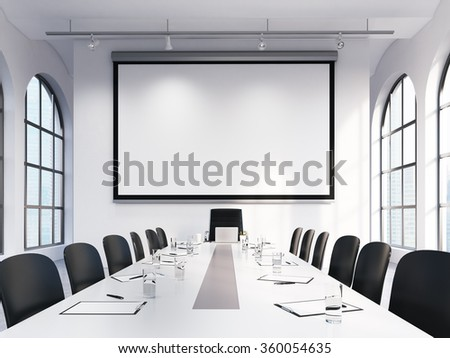 Light spacious meeting room in office building, big windows on two sides, big white table and black leather armchairs around, lamps above. White blank screen on the back wall. Concept of negotiations - stock photo