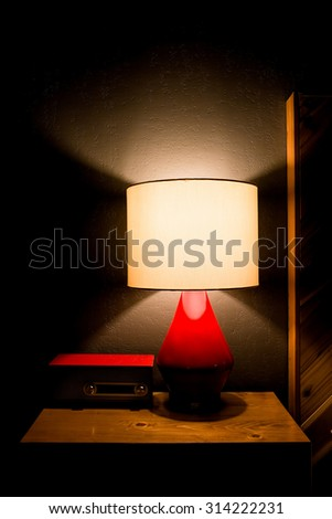 Light spill. Abstract. Red glossy lamp on a wooden nightstand. Interior design, home, hotel and fashion concept - stock photo