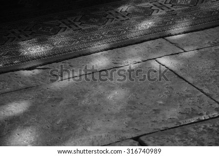 Light spots on the the floor and carpet in church. Sunlight filtered through the stained glass window. A game of light and shadow. Aged photo. Black and white. - stock photo