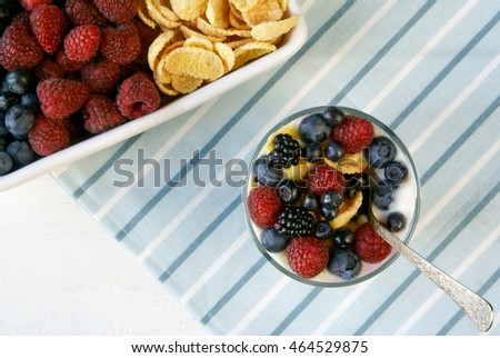 Light summer dessert for breakfast or a snack (cereal, oatmeal, fruit, yogurt) and a plate full of fruits and cornflakes. Rustic table, top view.