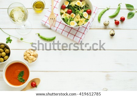 Light summer dinner / supper concept. Green salad with pasta, cherry tomato, quail eggs, olive oil. Cold tomato soup (gazpacho), croutons, green olives and glass of cold white wine.  - stock photo