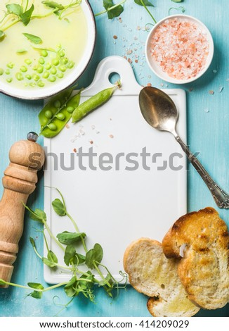 Light summer green pea cream soup in bowl with sprouts, bread toasts and spices. White ceramic board in the center, turquoise blue wooden background. Top view, copy space. Food frame concept - stock photo