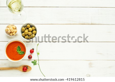 Light summer meal concept. Cold tomato soup (gazpacho), green olives, cherry tomato and glass of cold white wine. White table. Copy space. - stock photo