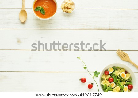 Light summer meal concept. Green salad with pasta, cherry tomato, quail eggs. Cold tomato soup (gazpacho) with croutons on a white table. Copy space.  - stock photo