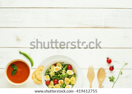 Light summer meal concept. Green salad with pasta, cherry tomato, quail eggs. Cold tomato soup (gazpacho) on a white table. Copy space.  - stock photo