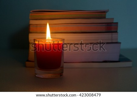 Light the candle with stack of books background,(low light condition) - stock photo