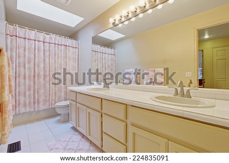 Light tone bathroom with skylight. Vanity cabinet with two sinks and large mirror. Bathroom decorated with pink curtain and rug
