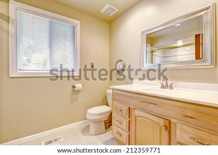 Light tones bathroom with ivory walls and wooden cabinet with mirror