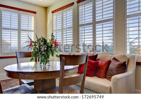 Light tones beautiful dining area  with a rustic dining table set, beige sofa and bright red pillows - stock photo