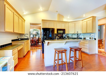 Light tones kitchen room with vaulted ceiling. View of kitchen island with stools
