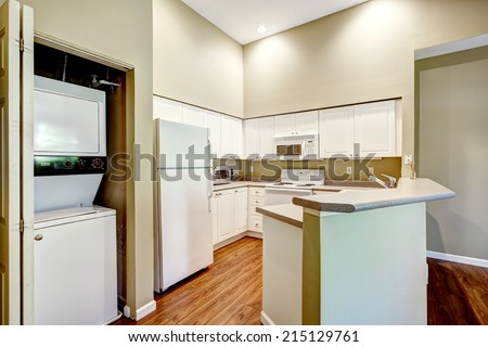 Light tones small kitchen room with laundry area - stock photo