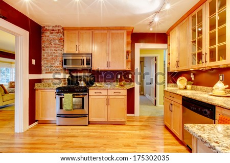 Light tones storage cabinets well matched with burgundy and brick designed wall - stock photo