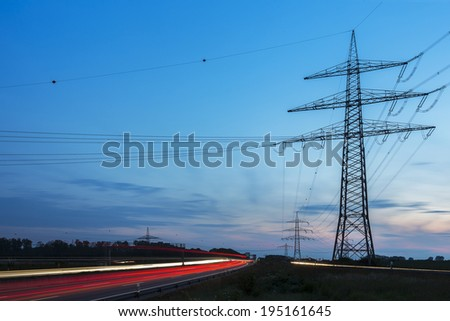 Light trails at blue hour at sunset with Electricity Pylon energy - stock photo