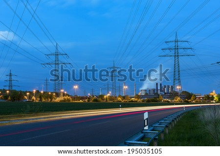 Light trails at night on a brown cole power station electricity Pylon landscape - stock photo