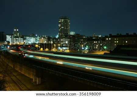 Light trails from a train arriving at London Victoria railway station at night - stock photo