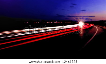 Light trails from two way traffic streaming along a highway at night. - stock photo