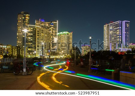 Light trails left by a pedicab on the James D. Pfluger Pedestrian and Bicycle Bridge with Austin skyline in the background.