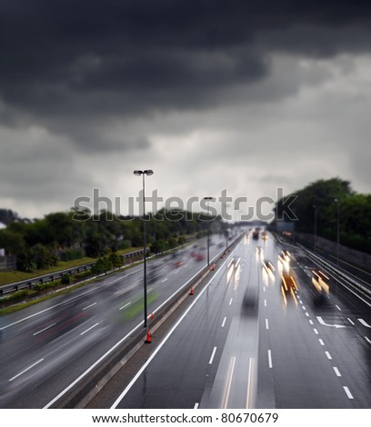 Light trails of motor vehicle traveling on a wet and slippery highway after a rainstorm against a overcast cloudy sky. - stock photo